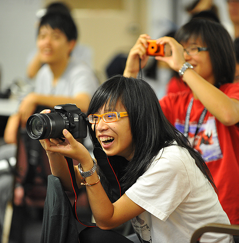 <p>UCAELI students take photographs of a a skit performed by their classmates during the summer closing ceremony held at the Bishop Center. Photo by Peter Morenus</p>