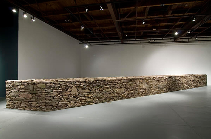 <p>Professor Olu Oguibe's construction of a 40-foot stone wall, highlighting the craftsmanship and social/cultural relevance of the stone wall to New England. Photo courtesy of Real Art Ways.</p>