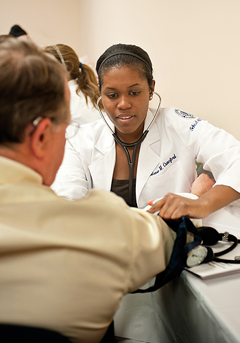 <p>Christine Crawford, a medical student, measures the blood pressure of a visitor to a clinic held at the East Hartford Community Health Center. Photo by Peter Morenus.</p>