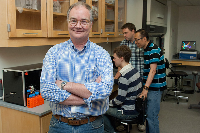 Professor Michael Lynes in his lab with, graduate students from left, Ryan Molony, Jamie Rice, and postdoctoral research associate Jongseol Yuk.