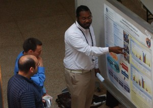 Ailton Coleman, who is pursuing a doctoral degree in public health, discusses his research with biomedical science students Brandon Albright and Kareem Mohni.