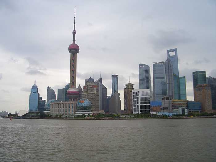 A daytime photo of the city of Shanghai, showing the Oriental Pearl Tower, formerly China's tallest building, at left.