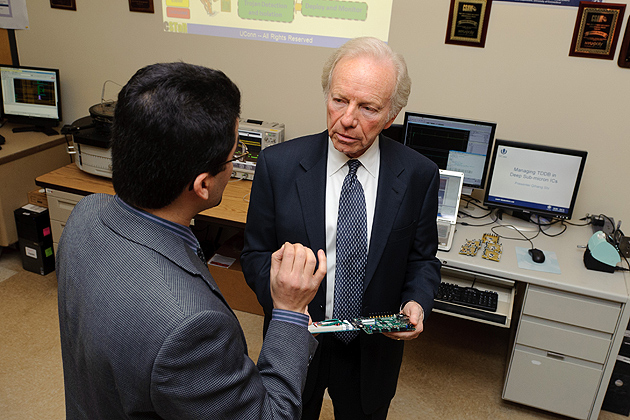 Mohammad Tehranipoor, director of the Center for Security Testing and Reliability, shows Sen. Lieberman an example of a hacked circuit board. (Peter Morenus/UConn Photo)