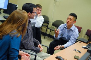 Cigna project manager John Kim, right, speaks with (left to right) Brittany DePoi '13 (ENG), Nhat-Tan Duong '13 (ENG), and Benjamin Luddy '13 (ENG), in the Cigna Innovation Lab. (Ariel Dowski '14 (CLAS)/UConn Photo)