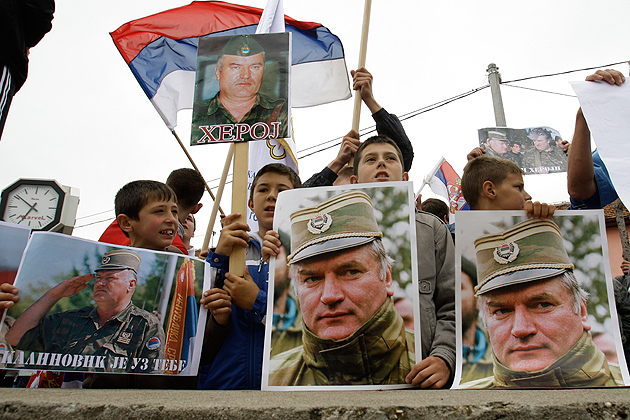 Bosnian Serb people holding Serbian flags and photos of former Gen. Ratko Mladic during a protest in Kalinovik, Bosnia, hometown of the Bosnian Serb wartime military leader, 70 kms southeast of Sarajevo, Sunday, May 29, 2011. Approximately 3,000 Bosnian Serbs, gathered to show support and anger after the arrest of Mladic. Protestors carried banners and flags and sang songs in his support, he was arrested after 16 years in hiding from the International War Crimes Tribunal in the Hague. Mladic is to face trial on 15 accounts of war crimes including genocide in Srebrenica in 1995. (AP Photo/Amel Emric)