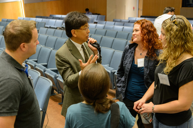 Edison Liu, president and chief executive officer, The Jackson Laboratory, center, speaks with Rachel O'Neill, professor of molecular and cell biology, and genetics and genomics graduate students between sessions. (Peter Morenus/UConn Photo)