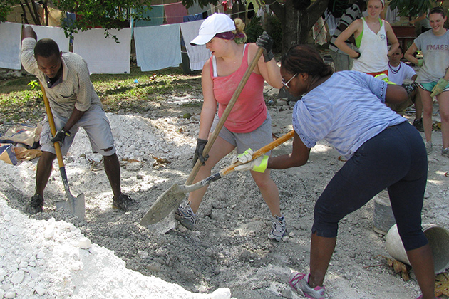 UConn students Caty Wagner, center, and Marissa Mack work with Hatian construction worker and translator Genois (Maxime) Manasse, left, to mix concrete for a housing project.  (Thomas Craemer/UConn Photo)