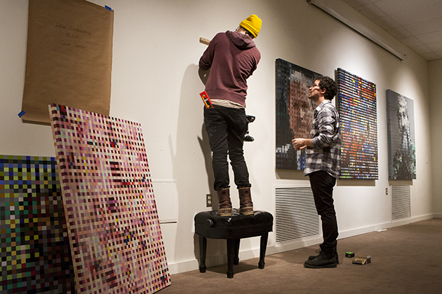 Russell Shoemaker '13 and Shane Morrisey '14 install the exhibition 4 Decades/ 4 Generations at the Jorgensen Art Gallery. (Sean Flynn/UConn Photo)