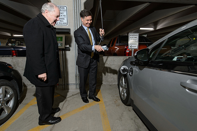 Dan Esty, right, DEEP commissioner, plugs in his electric car at the Storrs Center parking garage during a visit on April 16. At left is Daniel Shanahan of Control Modules of Enfield. (Peter Morenus/UConn Photo)