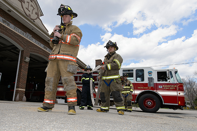 Volunteer firefighters Dave Keplesky, a sophomore at Eastern Connecticut State University, left, Danielle Struble '13 (CANR), John Levasseur, and Joe Molleur '13 (CLAS), practice pulling a hose from an engine at the Mansfield Fire Department on April 26, 2013. (Peter Morenus/UConn Photo)