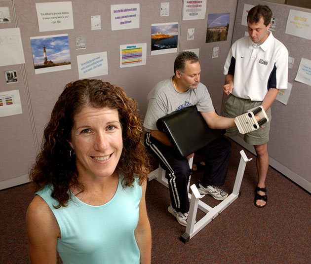 Linda Pescatello, Board of Trustees Distinguished Professor of Kinesiology, with a test subject and spotter demonstrating a weight training exercise. (File photo)