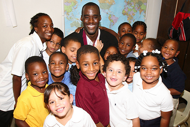 Former men's basketball player Emeka Okafor, with children at the Clark Elementary School in Hartford, after announcing his $250,000 gift to the Husky Sport program. In the back row, at left, is Lashika James, a paraprofessional at the school. Husky Sport, developed by kinesiology professor Jennifer Bruening, uses UConn students as mentors in nutrition and life skills, and encourages children to take part in sports and physical activities.