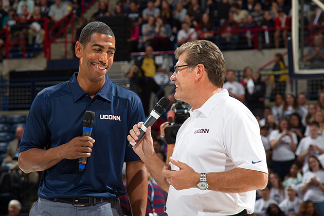 Men's basketball head coach Kevin Ollie, left, and women's basketball head coach Geno Auriemma engage in a friendly exchange at First Night in Gampel Pavilion on Oct. 18, 2013. (Steve Slade '89 (SFA) for UConn)