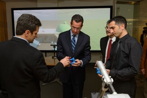 Horea Ilies, associate professor of mechanical engineering, left, Governor Dannel P. Malloy, Kazem Kazerounian, interim dean of engineering and Morad Behandish, a Ph.D. student of mechanical engineering examine objects from a virtual reality demonstration after a ceremony to commemorate the final approval of Next Generation Connecticut legislation held at the Information Technologies Engineering Building on Oct. 21, 2013. (Peter Morenus/UConn Photo)