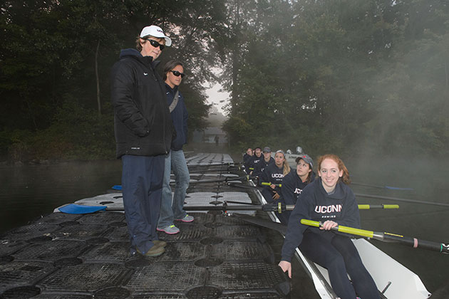Head coach Jennifer Sanford-Wendry, left, and assistant coach Allyson Zoppa '08 (CLAS), '09 MS give instructions to rowers as they board their shell at the start of practice. (Peter Morenus/UConn Photo)