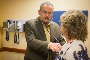 Craig Ryan MD meets with a patient at UConn Health Urgent Care at Storrs Center. (Peter Morenus/UConn Photo)