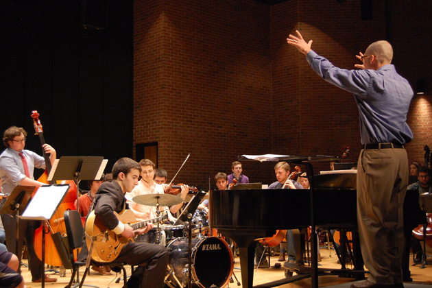 Earl MacDonald, associate professor of music, conducts the combined UConn Symphony Orchestra and Jazz Ensemble during a rehearsal for the premiere of his composition 'Dolphy Dance.' (Ken Best/UConn Photo)