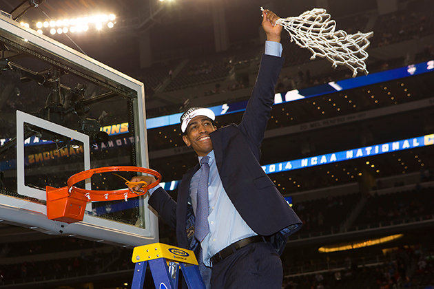 Head coach Kevin Ollie cuts down the net at the AT&T Stadium in Arlington, Texas. (Steve Slade '89 (SFA) for UConn)