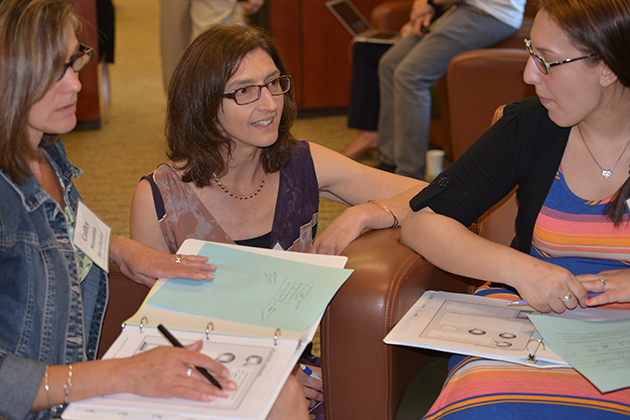 Megan Staples, associate professor of mathematics education, center, speaks with two teachers from Manchester High School, Cathy Mazzotta, left, and Adrianne Satin, during a workshop at the Neag School of Education. (Shawn Kornegay/UConn photo)