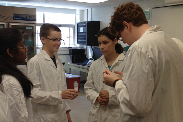 Microbiology Ph.D. student Emma White (right) distributes termites to KASET participants Sai Keerthi Manasanil, who will be entering South Windsor High School in the fall, Nicholas Michel, entering eighth grade in Tolland Middle School, and Hannah Leibowitz, who is also entering South Windsor High School. (David Colberg/UConn Photo)