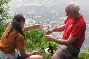 Dr. Kenneth Noll on the shores of Mirror Lake explaining biological collection techniques to KASET participant Hannah Leibowitz, from South Windsor. (Sheila Foran/UConn Photo)