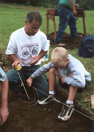 State Archaeologist Nicholas Bellantoni teaches his craft to a student at a summer science camp. (UConn File Photo)
