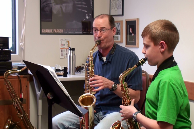 A music teacher instructs a young student how to play the saxophone at the Community School of the Arts. (Photo courtesy of CSA)