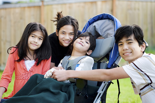 Five year old disabled boy in wheelchair lovingly surrounded by his three older brother and sisters (istock photo)