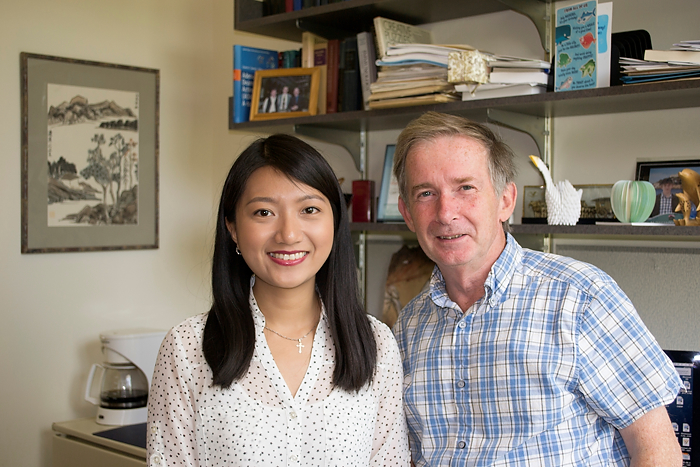 Xiaoxiao Hong, an incoming dental student who holds a doctoral degree in biomedical science at UConn Health, with her adviser, Gordon Carmichael. An example of Hong's artwork hangs on the wall. (Carolyn Pennington/UConn Health Photo)