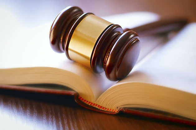 Gavel and open book on a wooden table in the courtroom. (iStock Photo)