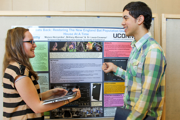 Brittany Marson, left, of Ludlow High School, and Moises Hernandez of Warren Harding High School, with their poster on efforts to restore the bat population. (Sheila Foran/UConn Photo)