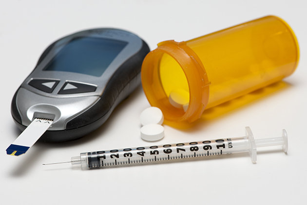 A glucometer, syringe, and pill pottle. (Shutterstock Photo)
