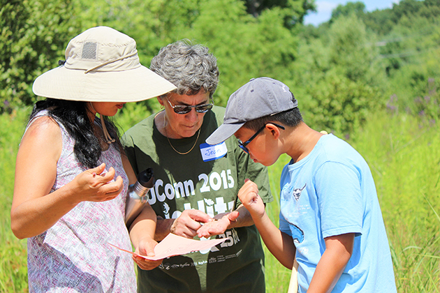 Alexander Fang, right, and his mother, left, consult with Jean Laughman, a UConn vounteer during BioBlitz 2015 on July 25, 2015. (Sheila Foran/UConn Photo)