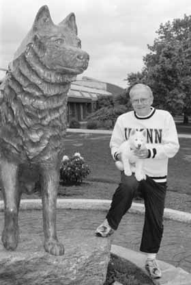 Former President Hartley with Jonathan XI as a puppy next to the bronze Husky statue in 1995.