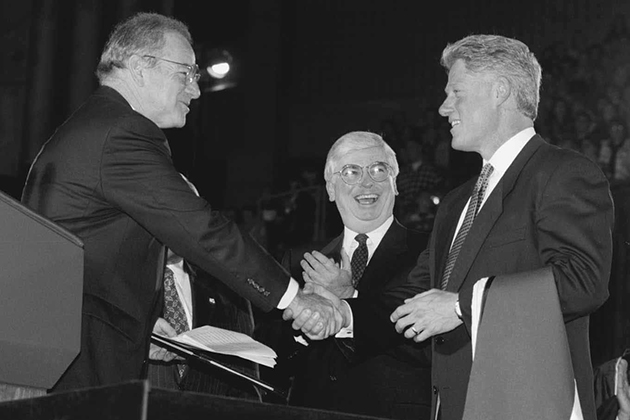 President Bill Clinton receives an honorary degree after his address in Gampel Pavilion on the occasion of the opening of the Thomas J. Dodd Research Center in October 1995. Lewis Rome, left, chairman of the Board of Trustees, presents the degree, as U.S. Sen. Christopher Dodd looks on. (Peter Morenus/UConn Photo)