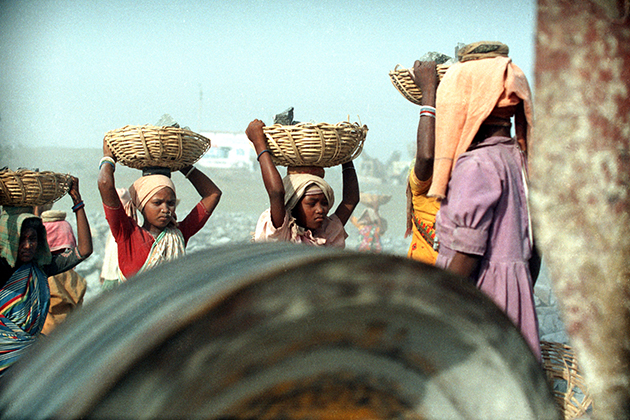 Girls carry heavy baskets of rock at a gravel quarry. (Robin Romano/UConn Archives & Special Collections)