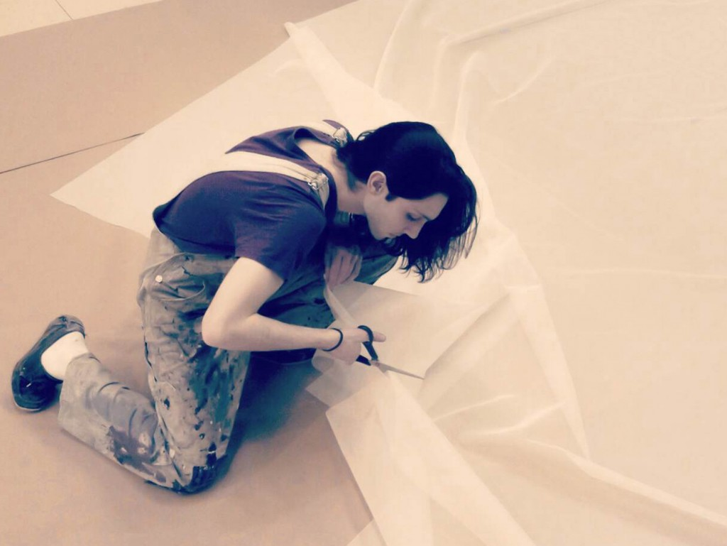 Antonio Campelli '15 cuts fabric while preparing one of his 'larger than life' installations. (Photo courtesy of Antonio Campelli)