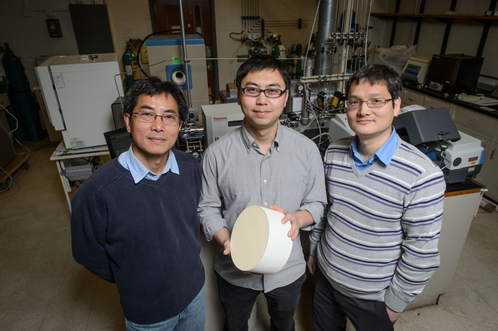 Industry mentor Wen Fu, left, Yanbing Guo, and Pu-Xian Gao with a sample of the catalyst they have developed. (Peter Morenus/UConn Photo)
