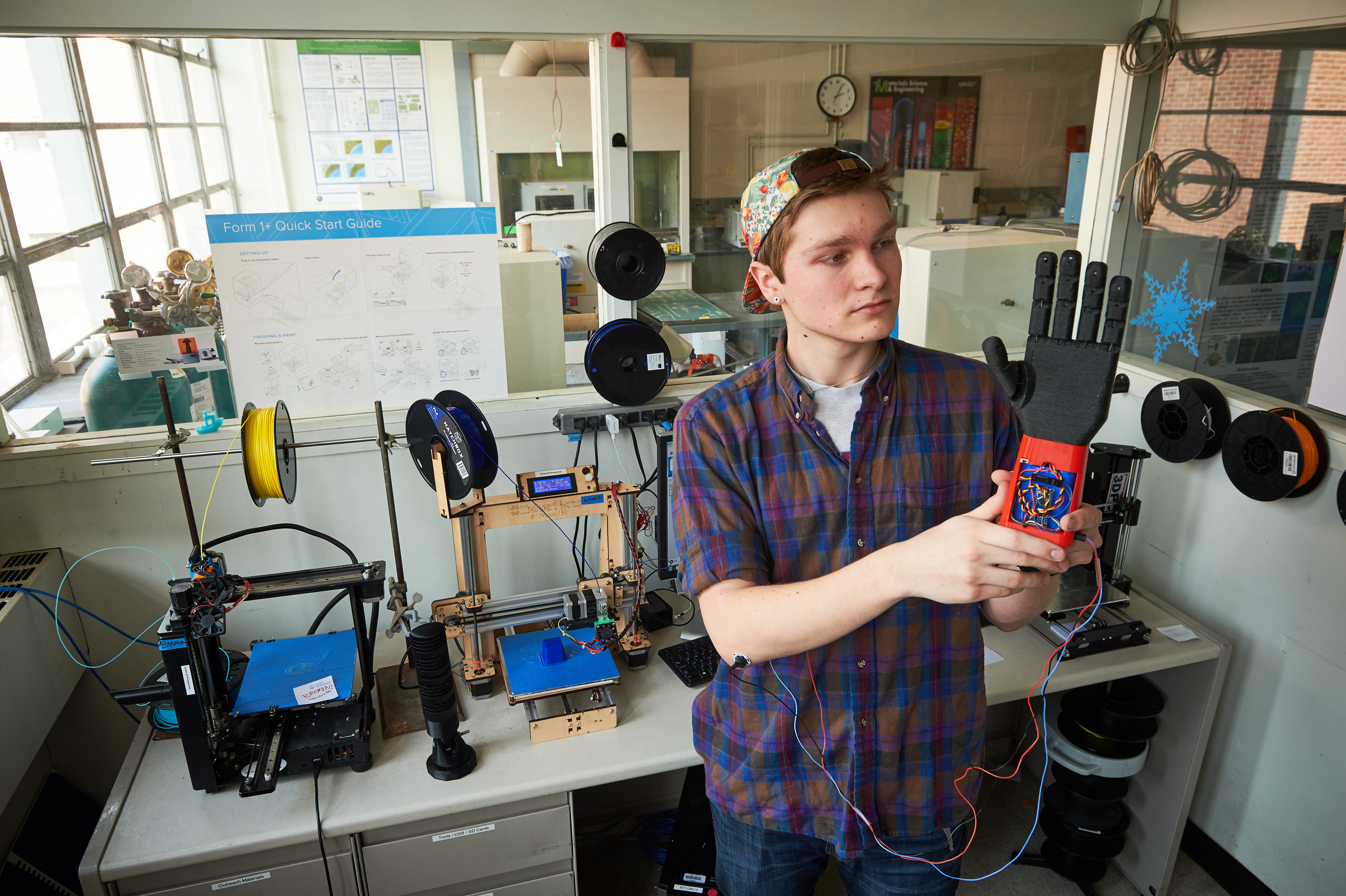 Stephen Hawes '17 (ENG) holds a 3-D printed prosthetic hand on Feb. 1, 2016. (Peter Morenus/UConn Photo)