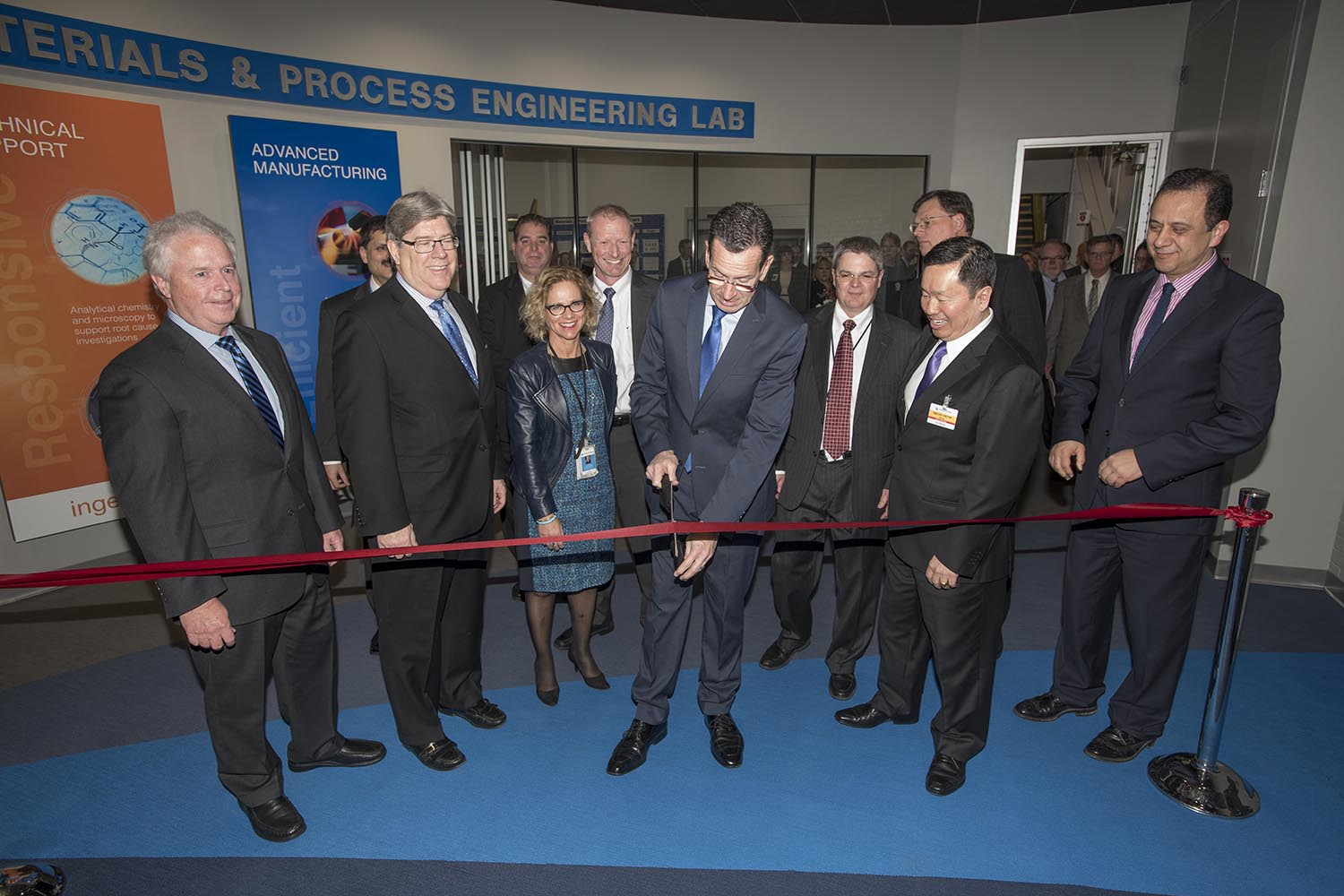 Governor Dannel P. Malloy cuts a ribbon at the new UTAS lab. Front from left to right is Dave Carter, Senior Vice President, Engineering, Operations and Quality, UTC Aerospace Systems, J. Michael McQuade, Senior Vice President of Science and Technology, United Technologies, Malloy, and UConn Provost Mun Choi, with other prominent United Technologies officials and dignitaries present.Governor Dannel P. Malloy cuts a ribbon at the new UTAS lab. Front from left to right is Dave Carter, Senior Vice President, Engineering, Operations and Quality, UTC Aerospace Systems, J. Michael McQuade, Senior Vice President of Science and Technology, United Technologies, Malloy, and UConn Provost Mun Choi, with other prominent United Technologies officials and dignitaries present.