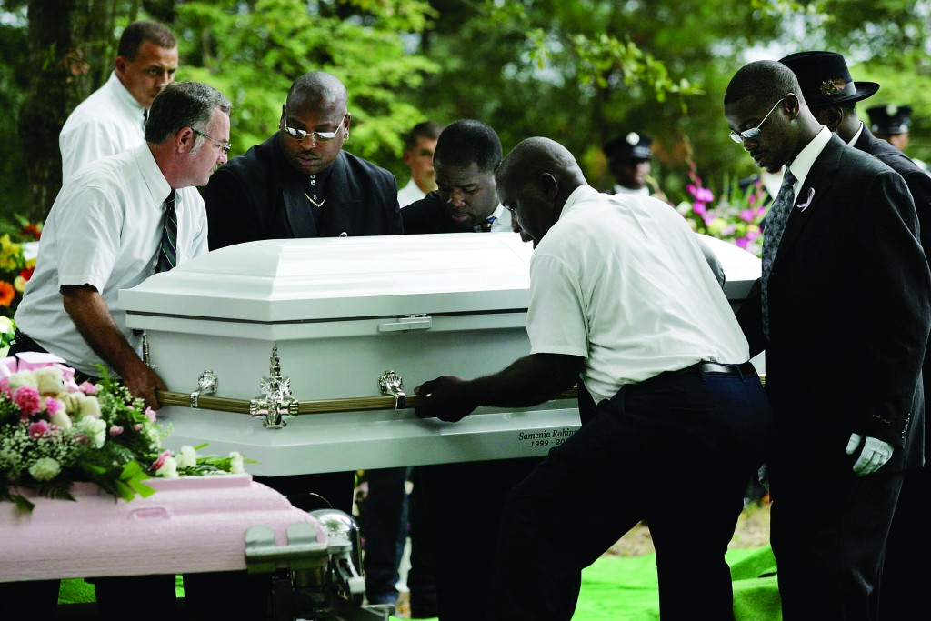 The casket of 6-year-old Samenia Robinson is laid to rest at alongside her mother Detra Rainey, 39, and three brothers William Rainey, 16, Hakiem Rainey, 13, Malachai Robinson, 8, at Hillsboro Brown Cemetery in West Ashley in 2006. Detra Rainey's husband was accused of fatally shooting her and his stepchildren inside their North Charleston mobile home. Alan Hawes/The Post and Courier (UConn Magazine photo)