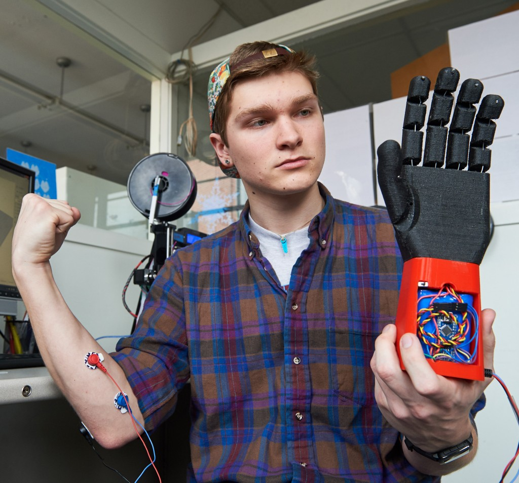 Stephen Hawes '17 (ENG) holds a 3D printed prosthetic hand on Feb. 1, 2016. (Peter Morenus/UConn Photo)