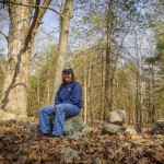 Manager of farm services Mary Kegler sits on the remains of a stone wall that once enclosed land used for grazing and crops. Large shade trees on the property will be retained for ecological and aesthetic purposes. (Sean Flynn/UConn Photo)