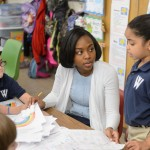 Symone James '16 (ED), a student teacher at W.B. Sweeney School in WIllimantic helps students with reading on April 26, 2016. (Peter Morenus/UConn Photo)