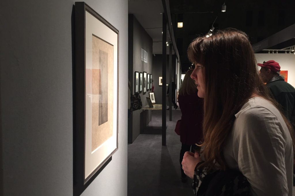 MFA candidate Kelsey Miller examines a print at the Independent Art Fair on Varick Street in New York. (Photo courtesy of students in ART 5310 Graduate Seminar)