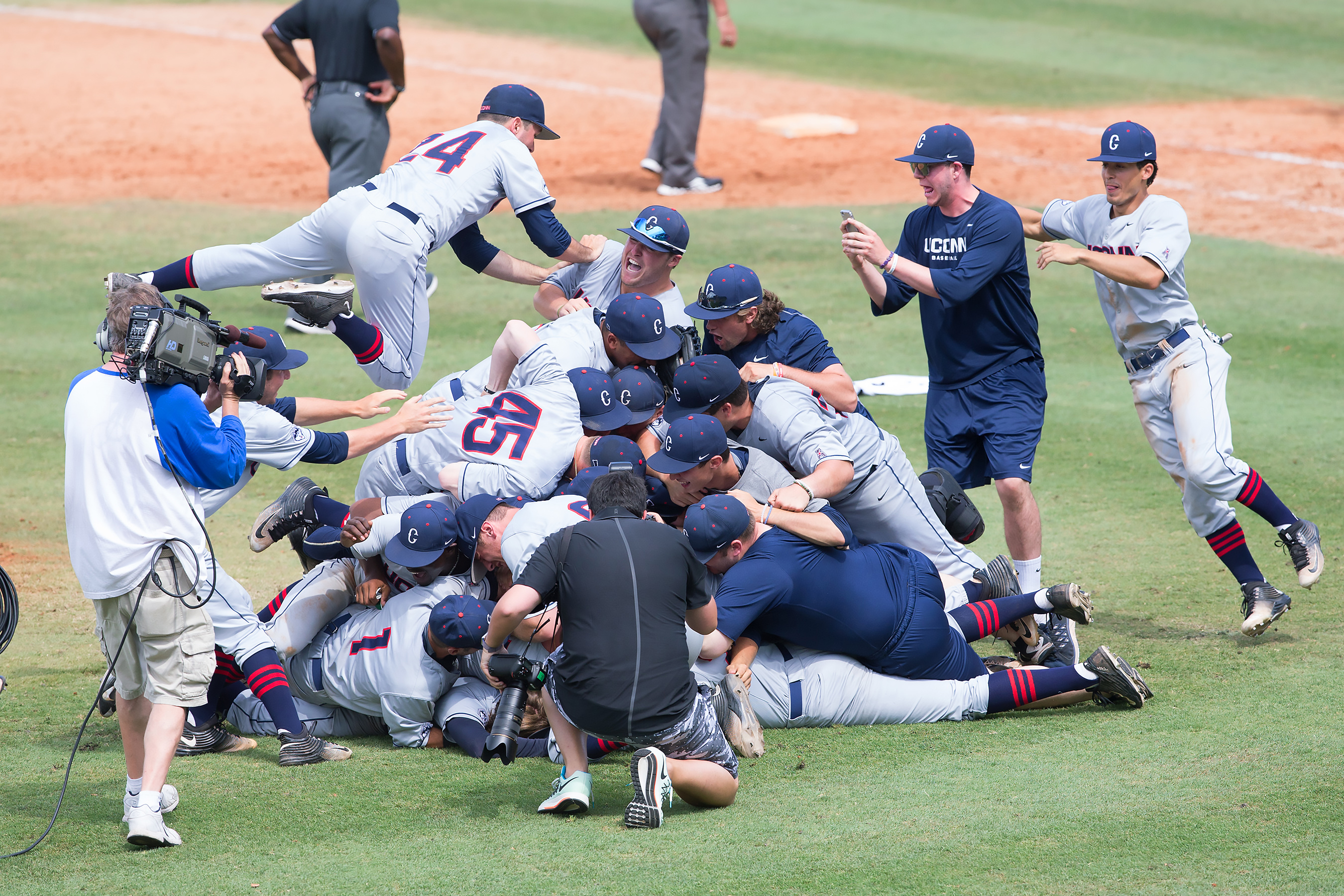 The team celebrates their 7-2 win over Houston to take the 2016 AAC Championship title. (Stephen Slade '89 (SFA) for UConn)