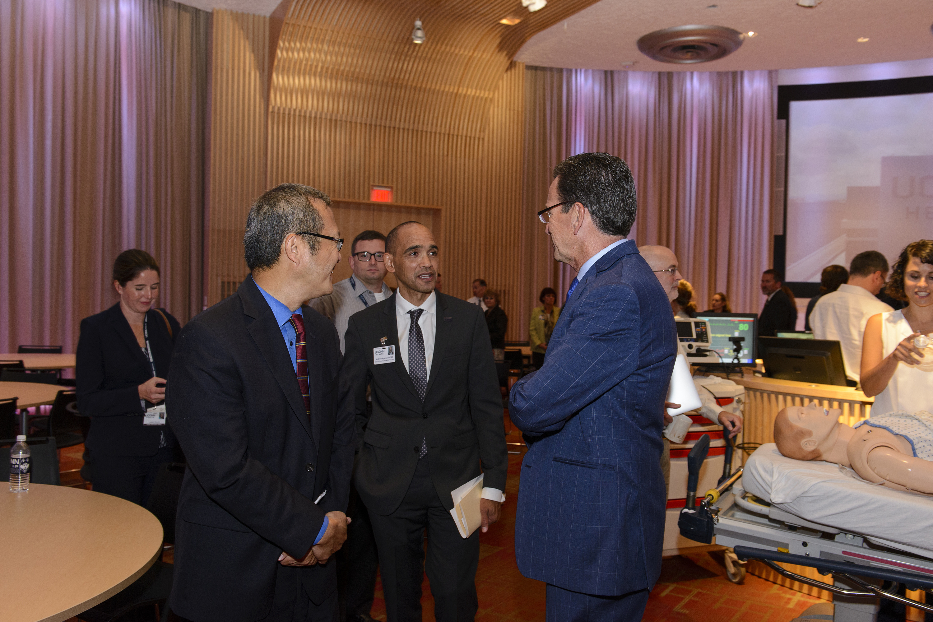 Gov. Dannel P. Malloy, right, speaks with Dr. Bruce T. Liang, left, and Dr. Andrew Agwunobi, during a ceremony at UConn Health Thursday to celebrate the opening of new biotechnology research space as part of the Bioscience Connecticut initiative. (Janine Gelineau/UConn Health Photo)