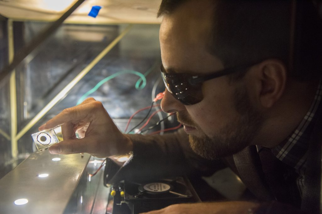 University of Connecticut researcher Justin Luria observes a sample of a cadmium telluride solar cell that is being tested under artificial sunlight in UConn's NanoMeasurements lab. (Photo by Ryan Glista/UConn)