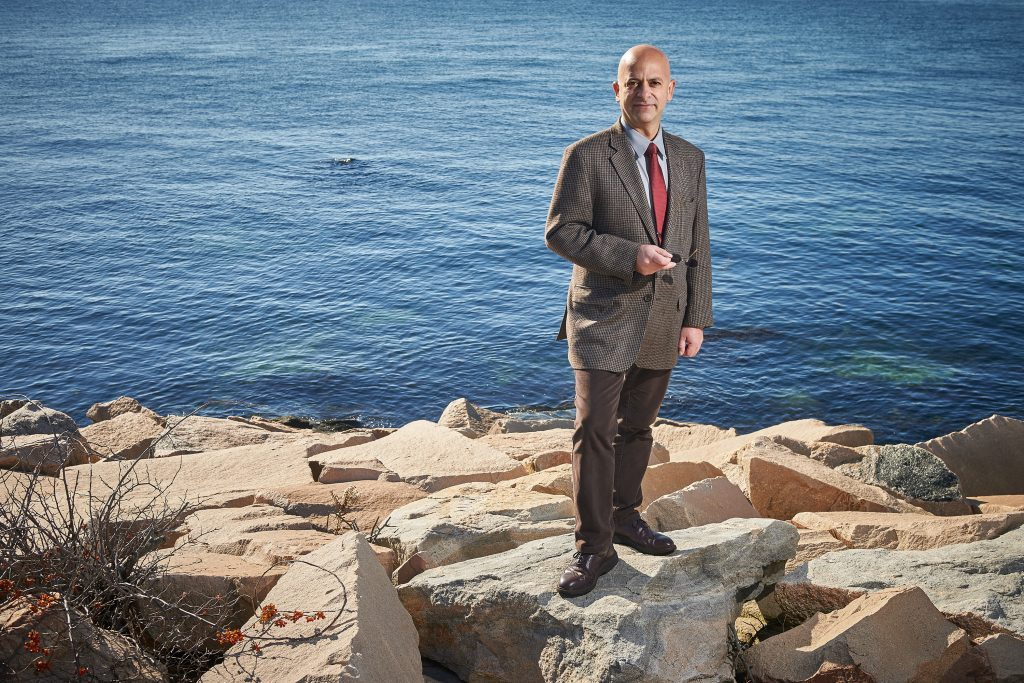 Kroum Batchvarov, an assistant professor in the Department of Anthropology who specializes in nautical archaeology, stands on the rocks beside Long Island Sound at the Avery Point campus. (Peter Morenus/UConn Photo)