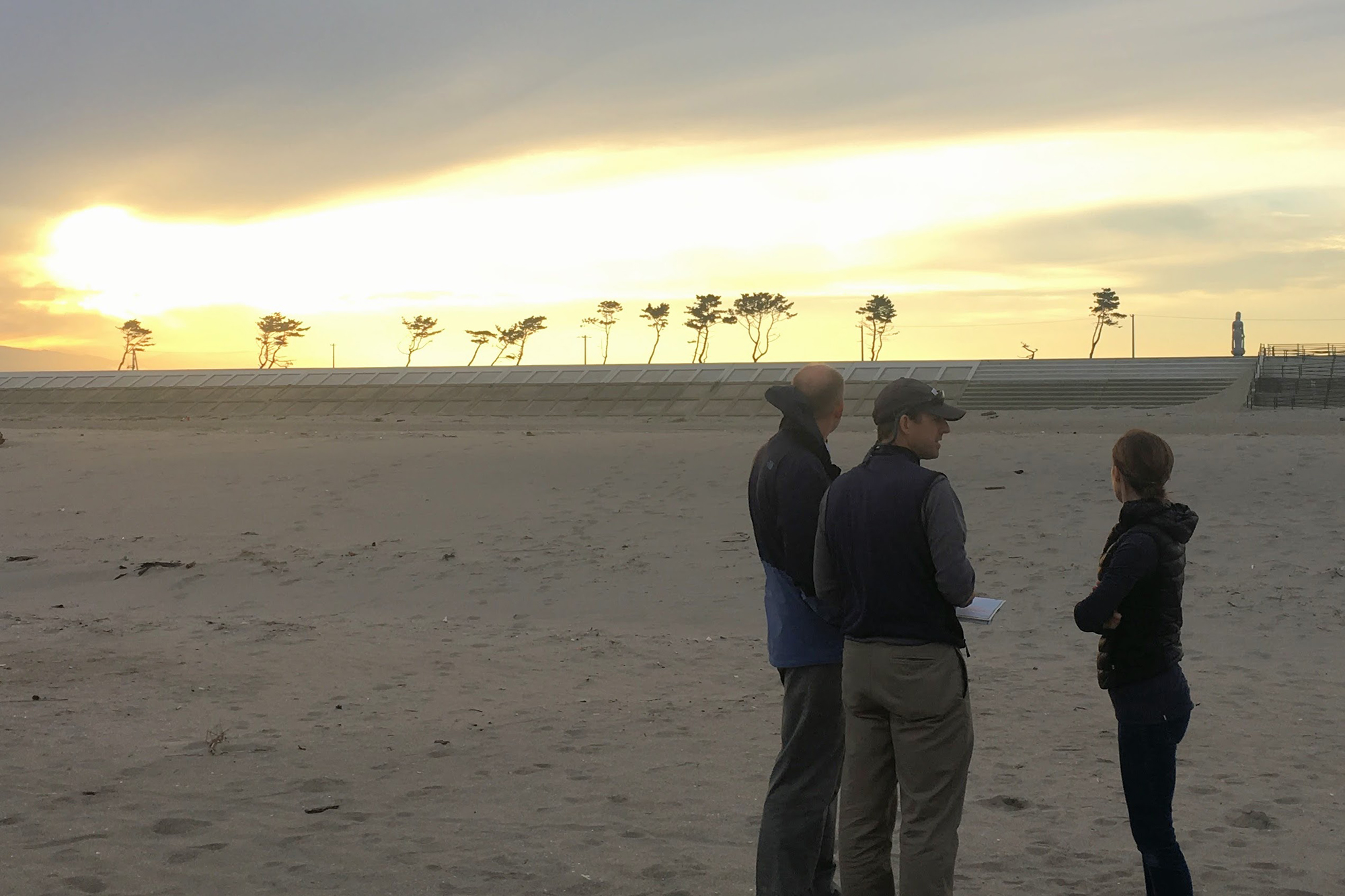 UConn professors on the beach near Sendai. Note the recently raised sea wall and trees with healthy branches indicating the height of the 2011 tsunami wave. (Photo courtesy of William Ouimet)